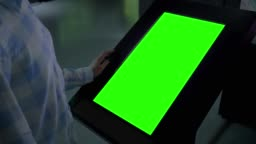 Green screen concept - woman looking at blank interactive green display kiosk