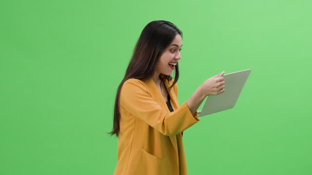 vidéos et rushes de écran vert excité femme asiatique surprise regardant l'écran d'ordinateur portatif - touche de couleur