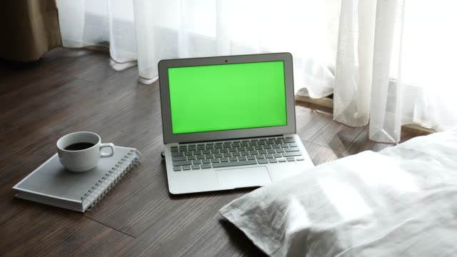 Green screen Laptop display with a book and a cup of coffee on the wood floor,Dolly shot
