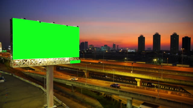 green screen of advertising billboard on expressway during the sunset with city background in bangkok, thailand - poster stock videos & royalty-free footage