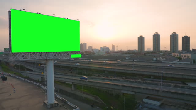 green screen of advertising billboard on expressway during the sunset with city background in bangkok, thailand. - poster stock videos & royalty-free footage