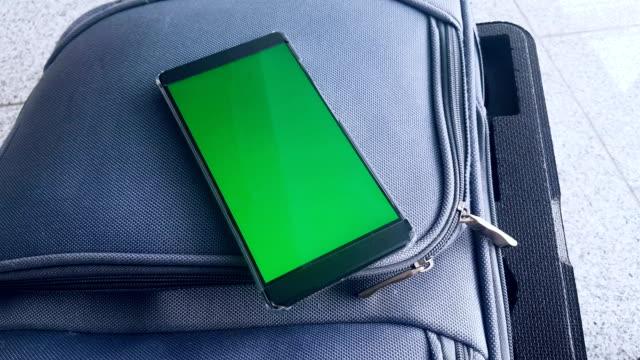 green-screen auf dem handy platziert auf einem koffer in einem flughafen - koffer stock-videos und b-roll-filmmaterial