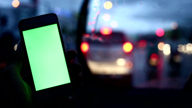 green screen, person using a smart phone on car