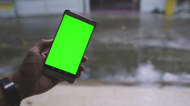 vídeos de stock e filmes b-roll de green screen smartphone and rain background at city with rain sound - atrás