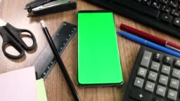 Green screen smartphone on the office table top view