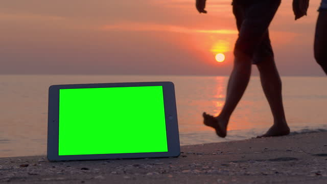 green screen tablet computer and tracking points on the beach while tourist walking in red sunsets over sea on vacation background.green screen on new technology concept. - silhouette stock videos & royalty-free footage