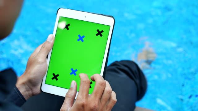 green screen tablet near swimming pool
