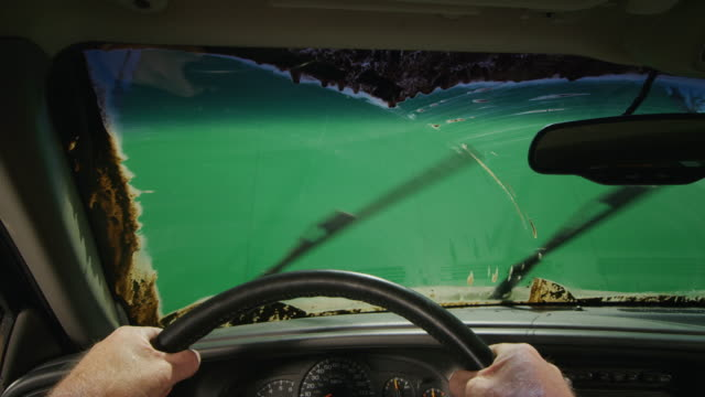 Green screen POV through a windshield completely covered with mud; the driver turns on windshield wipers to clear view.