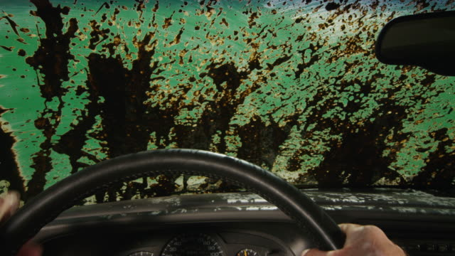 Green screen POV through a windshield covered in mud; the driver turns on windshield wipers to clear view.
