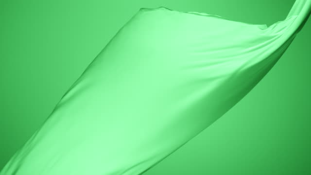vidéos et rushes de green silky fabric flowing by wind in green background, slow motion - souplesse