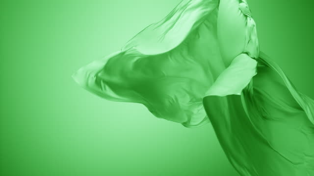stockvideo's en b-roll-footage met green silky fabric flowing by wind in green background, slow motion - flexibiliteit