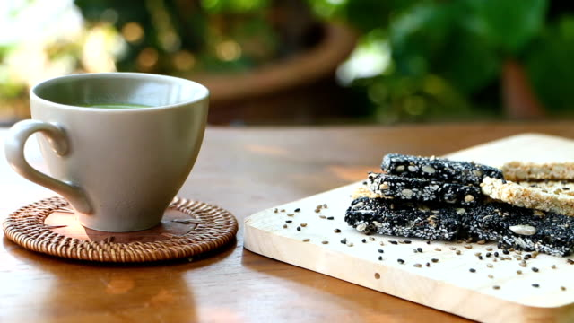 Green tea is ready to drink, put together with cereal, baked white sesame and sesame seeds put on wooden plates, food for people who need health care.