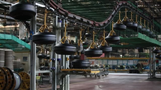 Green tires pass along an automated conveyor belt system after shaping at the Belshina JSC tire factory in Babruysk Belarus on Thursday March 16 2017