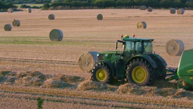 vidéos et rushes de green tractor making hay bales, cayton bay, north yorkshire, england - audio disponible en ligne