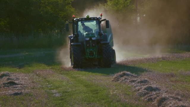 green tractor making hay bales, cayton bay, north yorkshire, england - traktor stock-videos und b-roll-filmmaterial