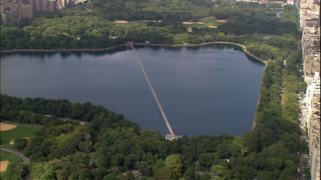 green trees surround the jacqueline kennedy onassis reservoir in central park. - reservoir stock videos and b-roll footage
