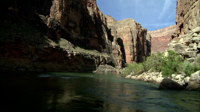 green vegetation contrasts with the grand canyon's red rock along a bend in the colorado river. - red rocks stock videos and b-roll footage