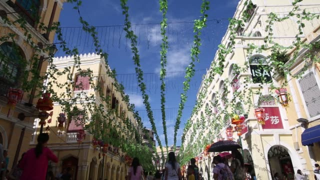 green vines are hung above senado square, pedestrians walk beneath green vines hung above senado square, pedestrians walk past a sa sa international... - leal senado square stock videos & royalty-free footage