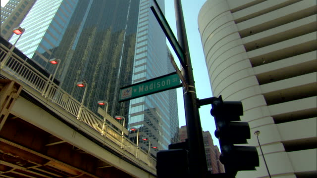 "green ""w madison st"" street sign on traffic light pole, elevated train tracks & partial buildings bg, - chicago elevated stock-videos und b-roll-filmmaterial"