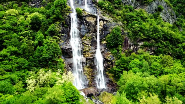 green waterfall on the mountain in switzerland
