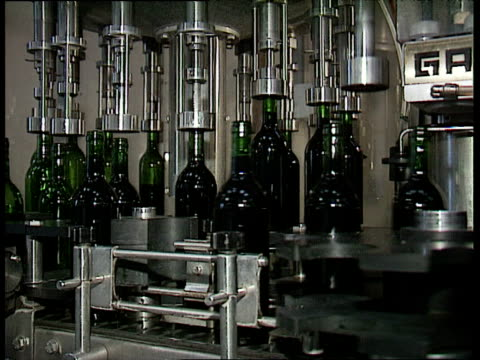 vidéos et rushes de green wine bottles move along production line as corks are mechanically placed into bottle necks in wine making factory france - chaîne de production