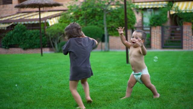 greenery - children playing in the garden - seifenblasenring stock-videos und b-roll-filmmaterial
