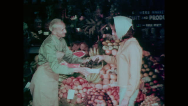 1967 greengrocer offers female shopper a plum, which she eats happily - greengrocer stock videos & royalty-free footage