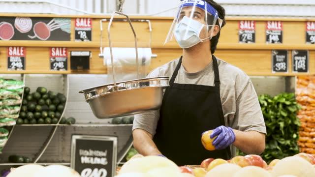 vídeos y material grabado en eventos de stock de empleado de greengrocers poniendo manzanas en una báscula usando una máscara protectora para la cara, un protector facial y guantes protectores - trabajador de primera línea