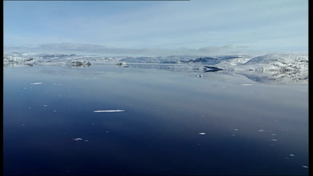 air views of glaciers greenland ext air views glacier showing dark edges of rock protruding from snow calm sea in the background track / air views... - uneven stock videos & royalty-free footage