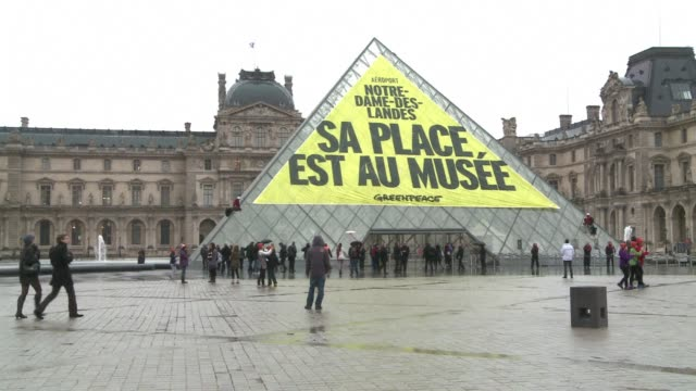 vídeos de stock e filmes b-roll de greenpeace activists covered one side of the louvres iconic glass pyramid with a large banner on thursday to denounce a new french airport project on... - pyramid