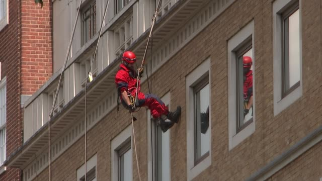 vidéos et rushes de greenpeace protesters block bp head office in london; england: london: st james's square: ext greenpeace protester abseiling down façade of bp... - office block exterior