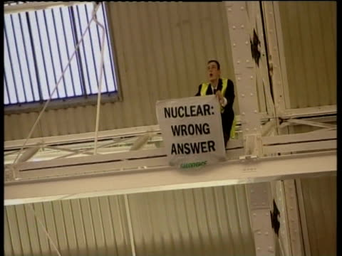 greenpeace protestor on roof inside hall at confederation of business industry conference holds anti nuclear banner london; 29 nov 05 - greenpeace stock videos & royalty-free footage