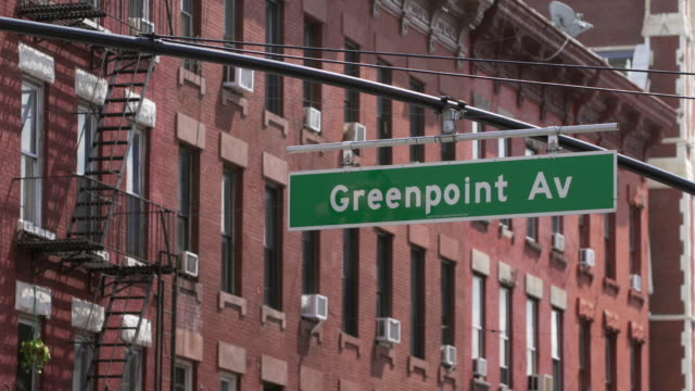 Greenpoint Av street sign against a Brooklyn apartment building in background.