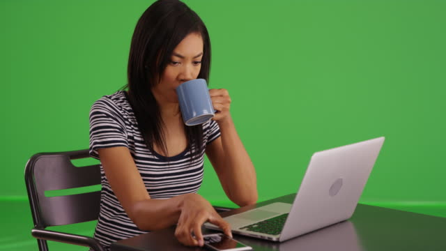 greenscreen shot of black woman texting with phone and typing on computer - weibliche angestellte stock-videos und b-roll-filmmaterial