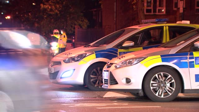 overnight general views ENGLAND London Greenwich GVs police cordon on Armitage Road including street sign 'Armitage Road SE10' / forensic officers at...