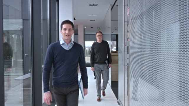 slo mo pov greeting coworkers in the hallway - business casual stock videos & royalty-free footage