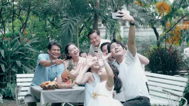 vídeos de stock e filmes b-roll de greeting with video conference: thai family using phone for selfie after barbecue grill party at the front of backyard - asiático e indiano