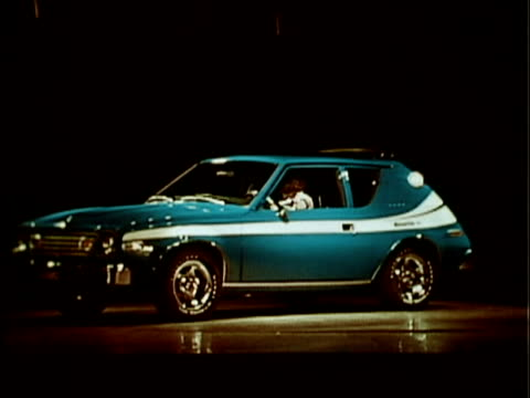 stockvideo's en b-roll-footage met 1976 montage 1977 amc gremlin slowly revolving on turntable onstage / usa - toonzaal