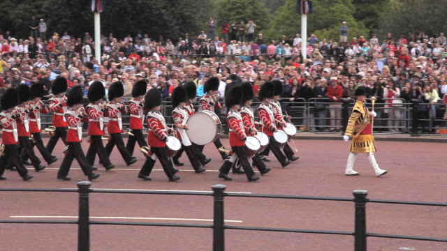 vídeos de stock e filmes b-roll de grenadier guards band marches near to buckingham place in the mall at london - banda de marcha