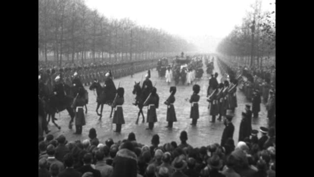 Grenadier Guards line rainy street as the Gold State Coach bearing George V and Queen Mary approaches on its way to the State Opening of Parliament /...