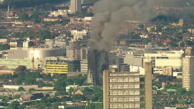 12 deaths confirmed aerials of burning building ENGLAND West London of Grenfell Tower block on fire black smoke belching into air and firefighters on...