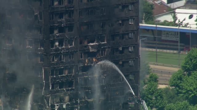 12 deaths confirmed aerials of burning building AIR VIEWS of Grenfell Tower block fire showing charred and blackened building and black smoke...