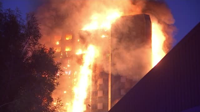 12 deaths confirmed emmanuel adegoke interview sot wide shot grenfell tower fire with ambulances in foreground long shot fire pan fire near top of... - 手を振る点の映像素材/bロール