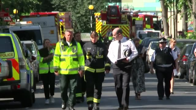12 deaths confirmed ENGLAND London EXT Smoke rising from smouldering Grenfell Tower / Emergency Services officials towards along road Dany Cotton...