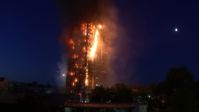 12 deaths confirmed ENGLAND London Latimer Road Wide shot Grenfell Tower during fire Long shot windows lit up by flames Low angle shot person waving...