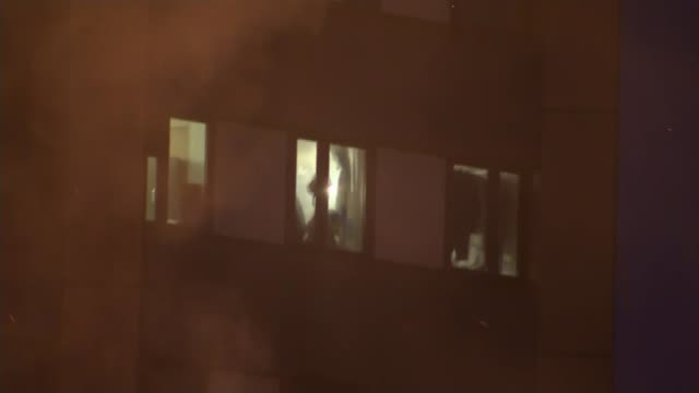 12 deaths confirmed People at window waving as debris falls from upper floors Person waving from window Silhouette of person at window waving