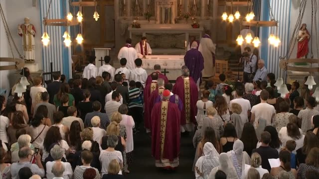 at least 58 people now presumed dead north kensington st pius x catholic church int high angle view of clergy along inside church during mass for... - itv weekend evening news点の映像素材/bロール