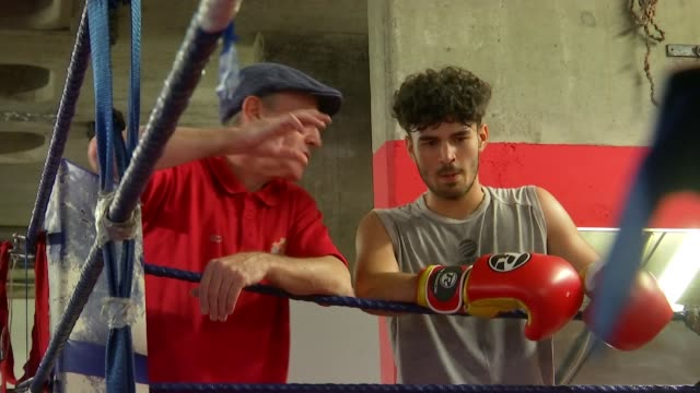 dale youth boxing club lost in fire england london int man training boy to box in ring boys sparring boy hitting punch bag gary mcguinness chatting... - youth club stock videos & royalty-free footage