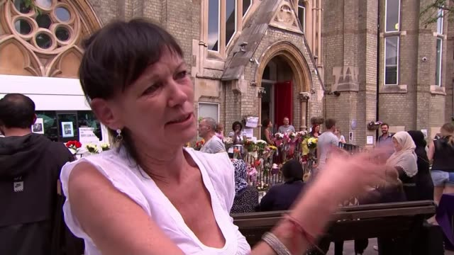 vidéos et rushes de effect on local community; england: london: kensington: ext people along outside notting hill methodist church woman placing flowers at makeshift... - multi layered effect