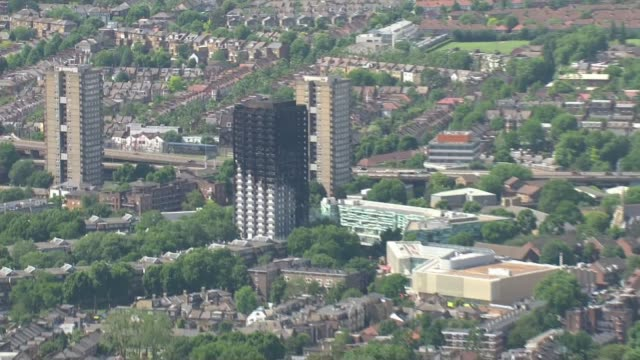 vídeos de stock, filmes e b-roll de fire investigation work continues / tower block safety north kensington view / aerial burntout ruin of grenfell tower zoom out to surrounding west... - rodeando